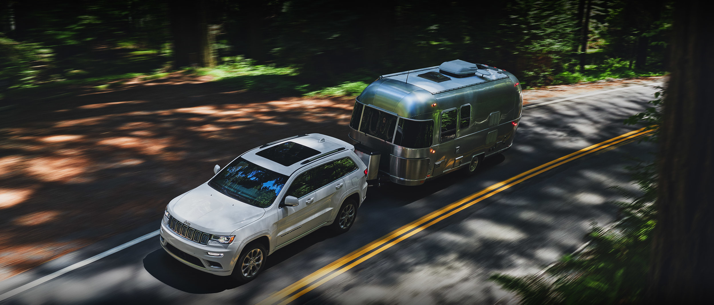 White 2020 Jeep Grand Cherokee towing a large silver RV.