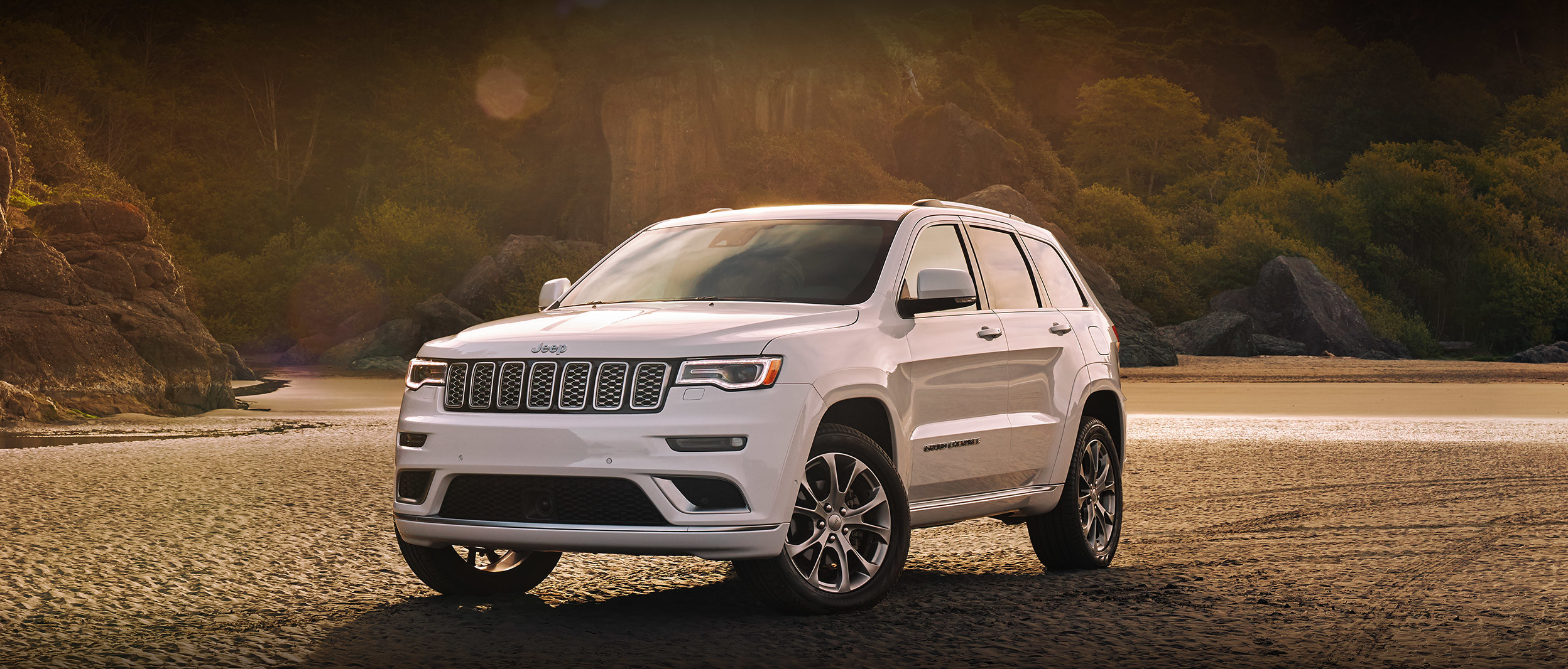 White 2020 Jeep Grand Cherokee, parked on beach sand, near a forest.