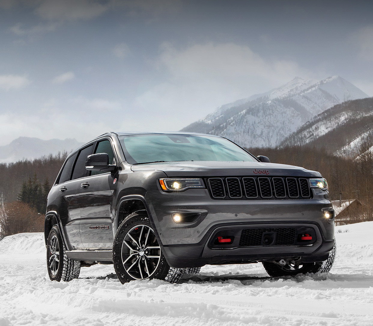 Front view of the 2020 Jeep Grand Cherokee Trailhawk in grey parked on a snow-covered road