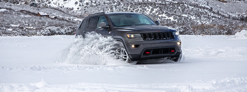 Front view of the 2020 Jeep Grand Cherokee Trailhawk in grey, driving through a snow-covered field in the mountains