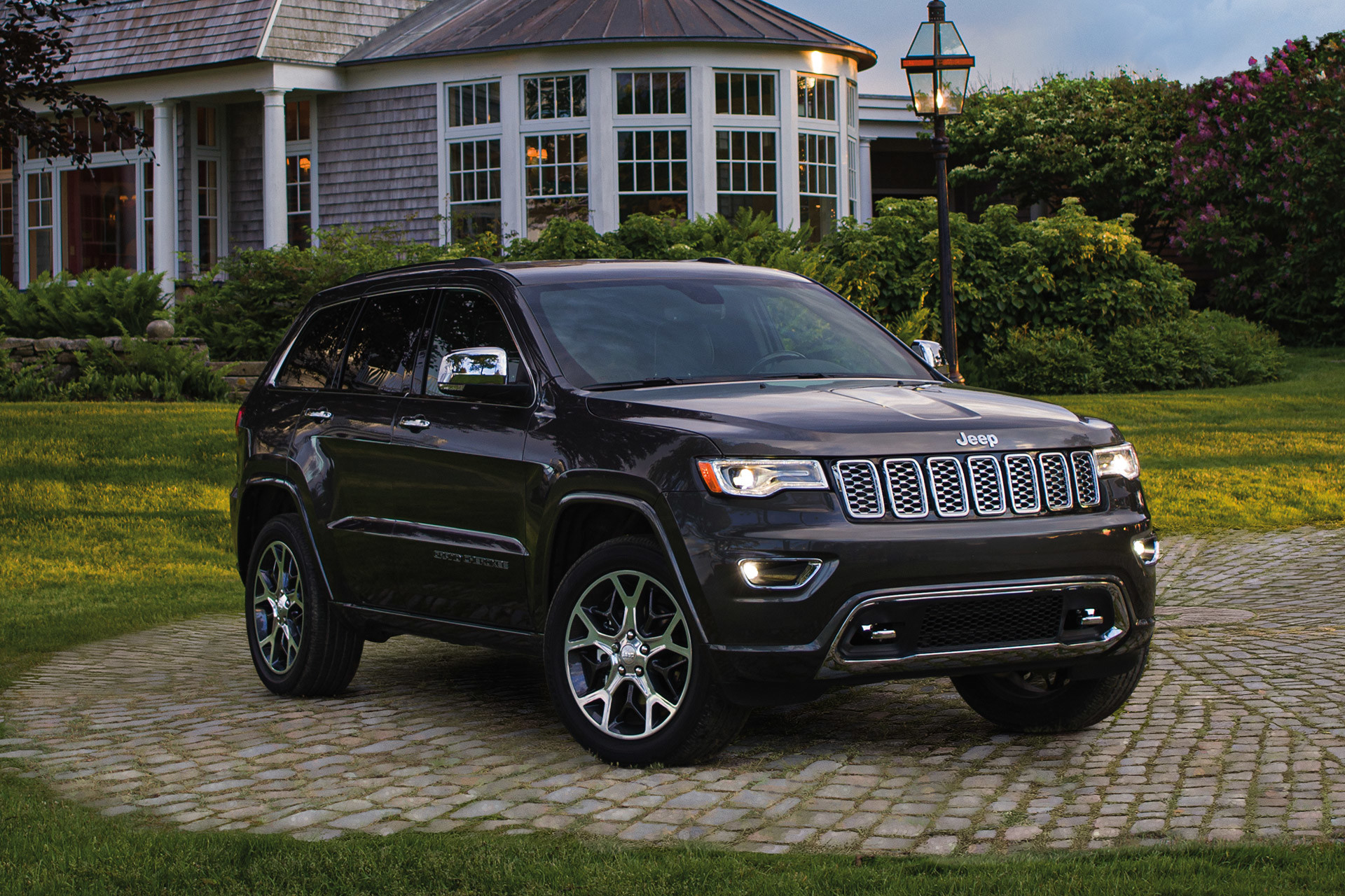 Navy blue Jeep Grand Cherokee parked in front of a large house surrounded by shrubs and grass.