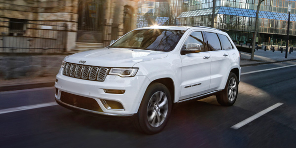 Jeep Grand Cherokee 2021 blanc parcourant des routes urbaines