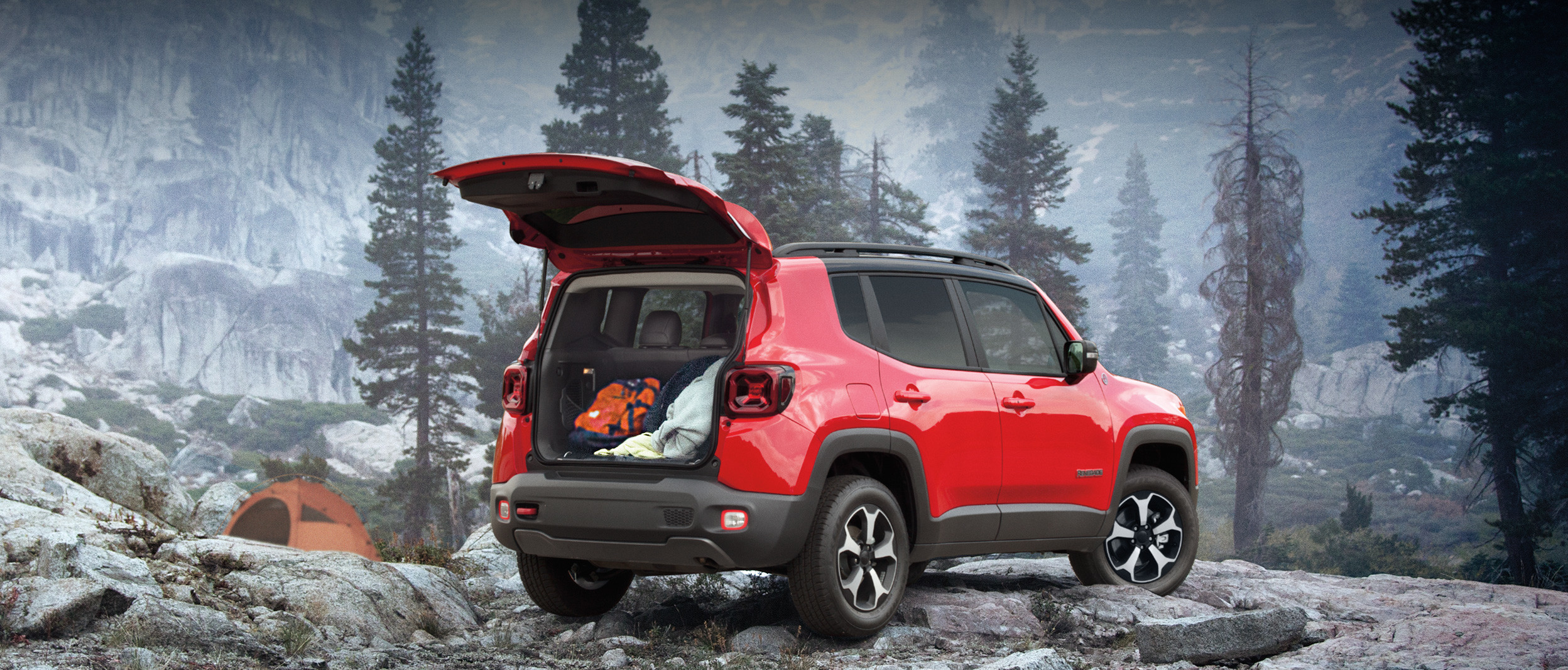Rear view of the 2020 Jeep Renegade in red parked in a rocky forest in the mountains, while a man cooks on a camping stove nearby