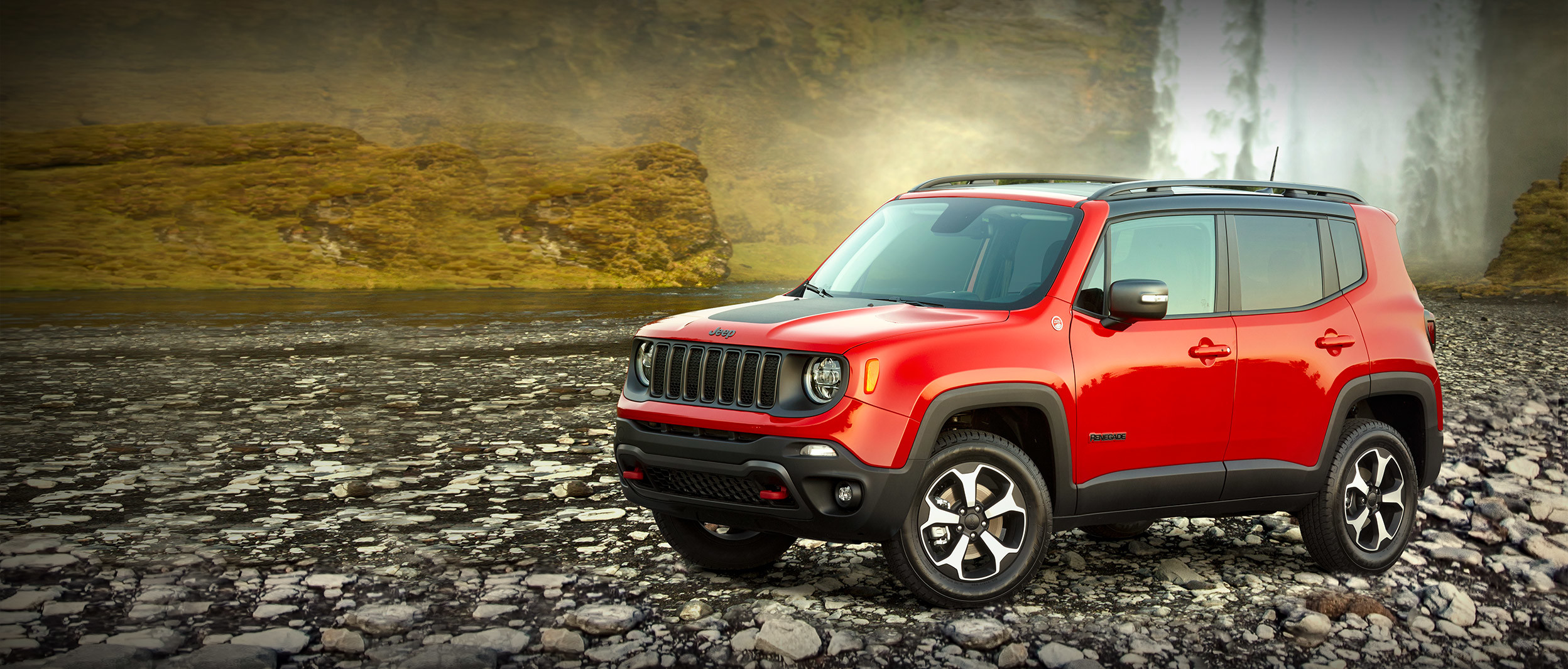 2019 Jeep Renegade red exterior parked in front of a waterfall.