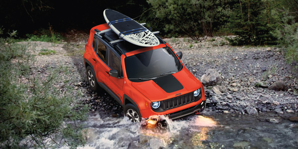 Red 2021 Jeep Renegade with a paddle board on the roof rack driving through a stream