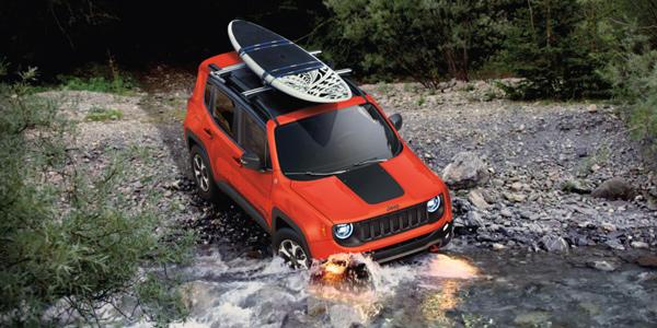 Jeep Renegade 2021 rouge transportant une planche à bras sur son porte-bagages de toit franchissant un ruisseau