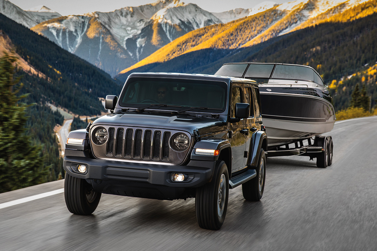2019 Jeep Wrangler driving over sand dune, shown in silver