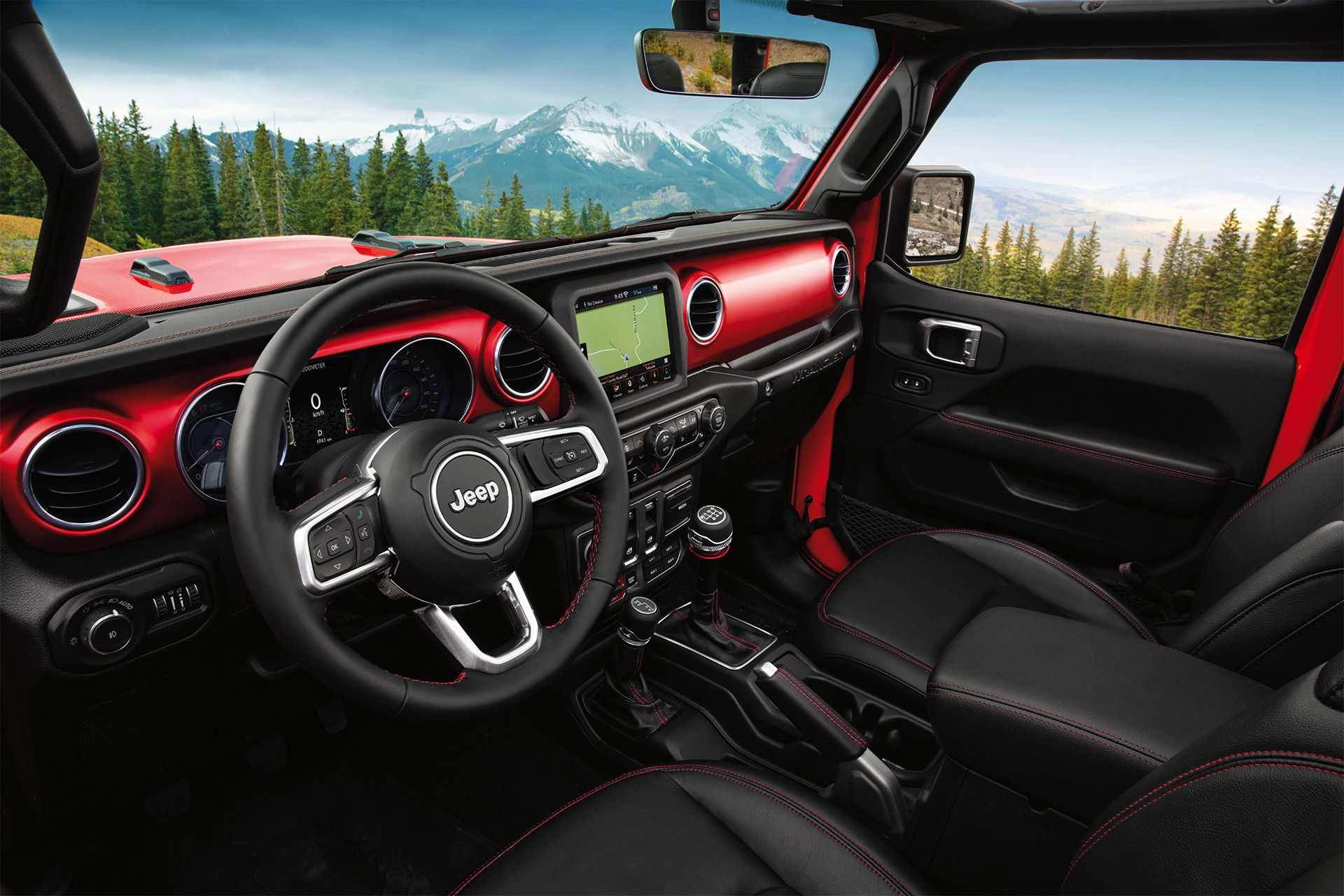 2019 Jeep Wrangler Rubicon interior showing front bucket seats with red stitching and jeep grille logo
