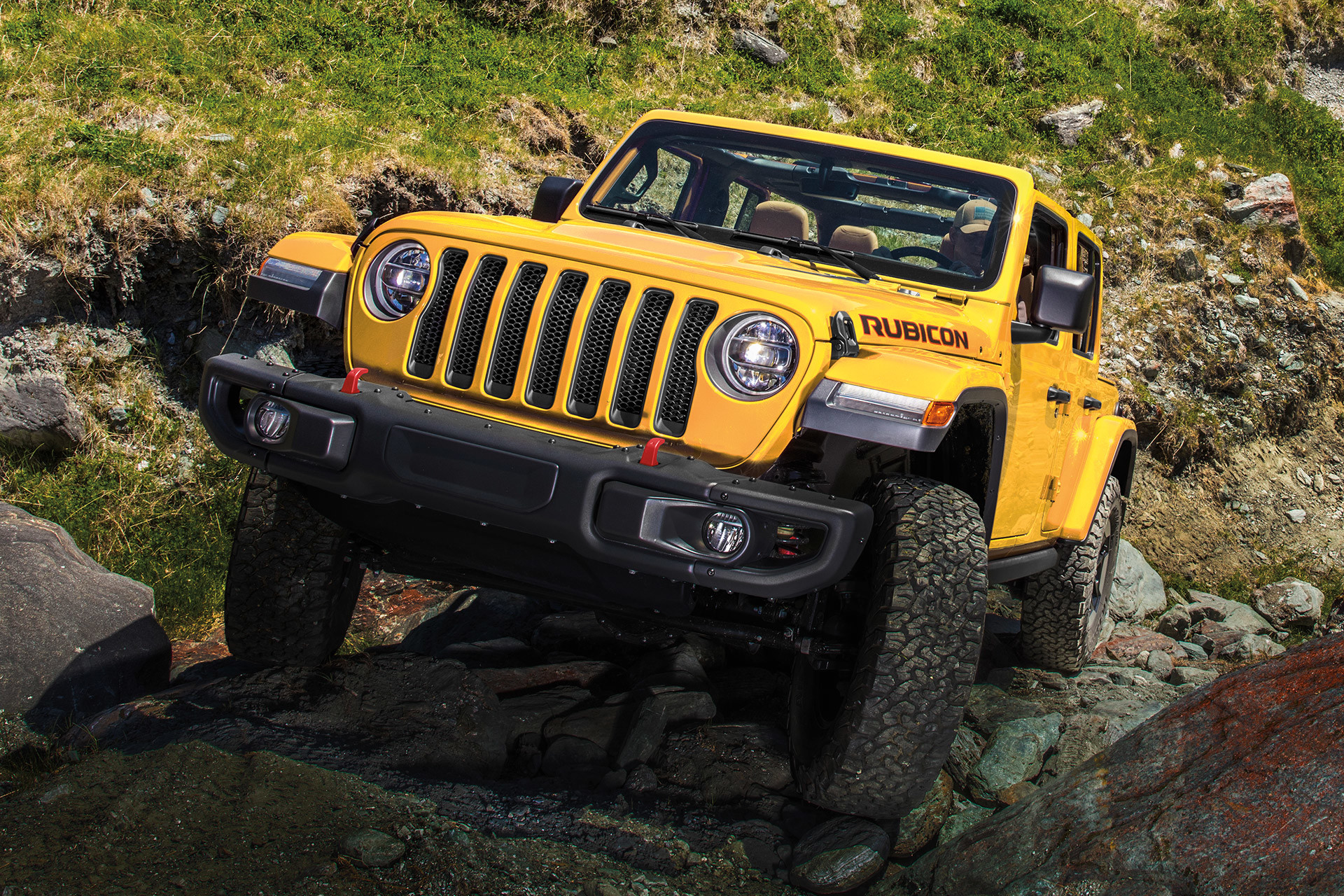 2019 Jeep Wrangler exterior, shown in red driving over rocks