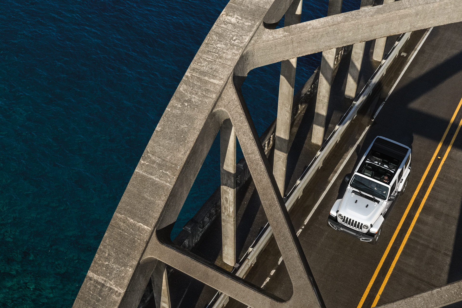 2019 Jeep Wrangler crossing a bridge, shown in white