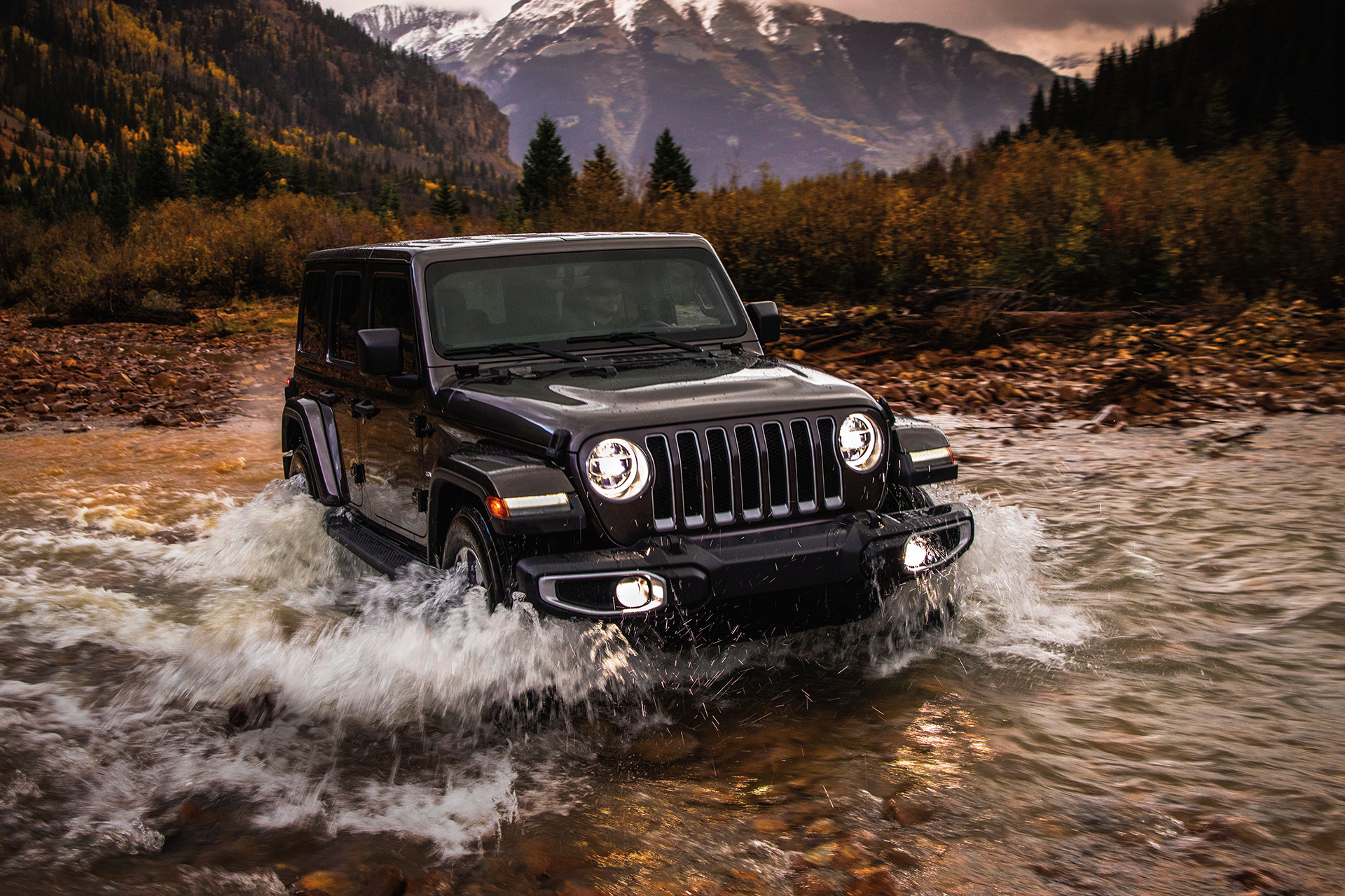 2019 Jeep Wrangler fording through shallow water, shown in black