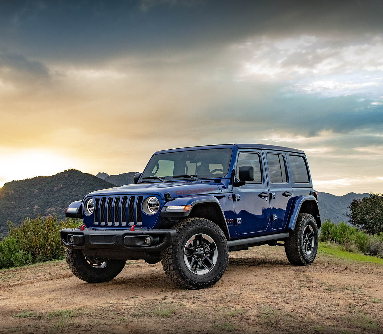 2019 Wrangler Unlimited Rubicon in Ocean Blue parked on hilltop, mountains behind.