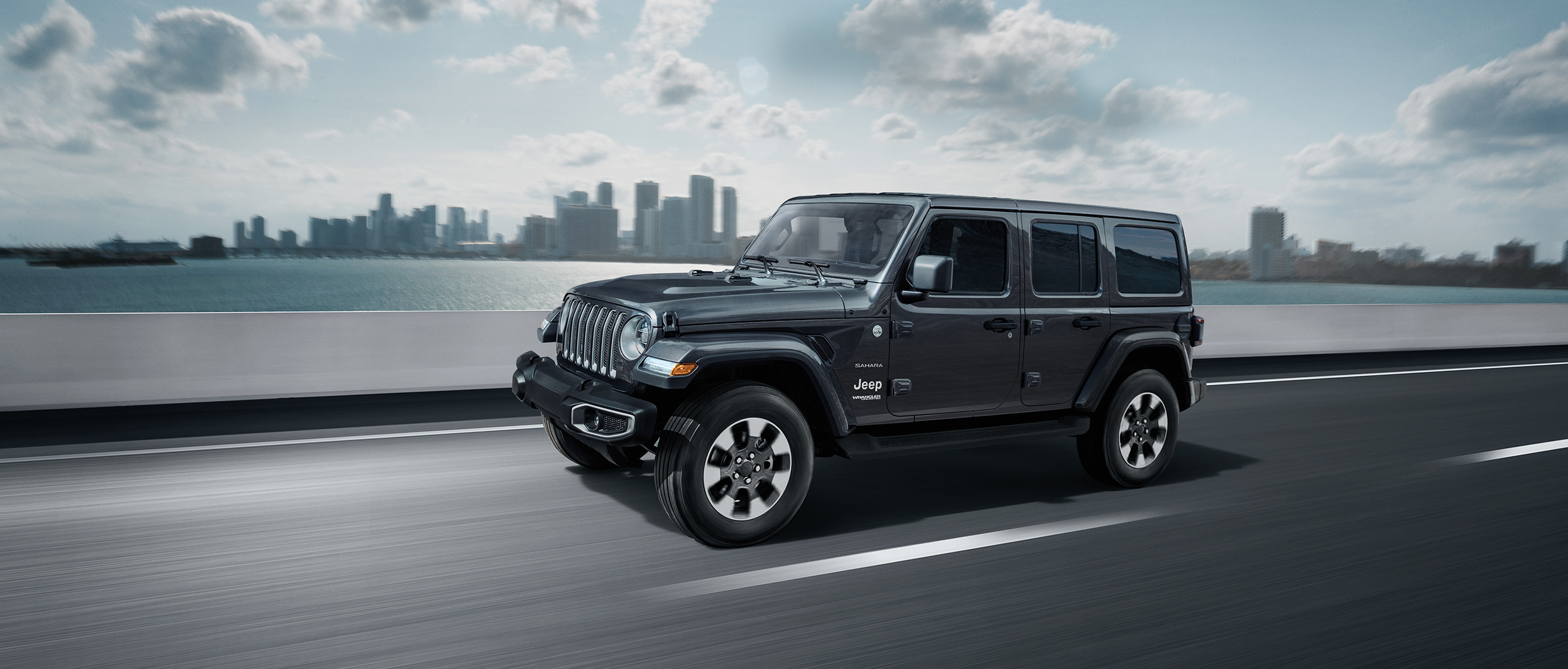 2019 Jeep Wrangler on highway, shown in dark grey