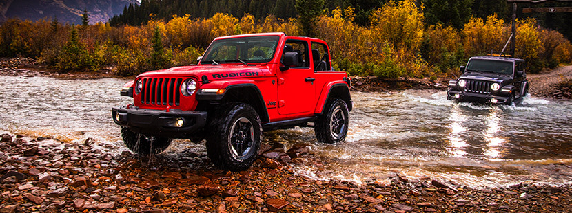 2019 Jeep Wranglers on shallow river, shown in red and grey