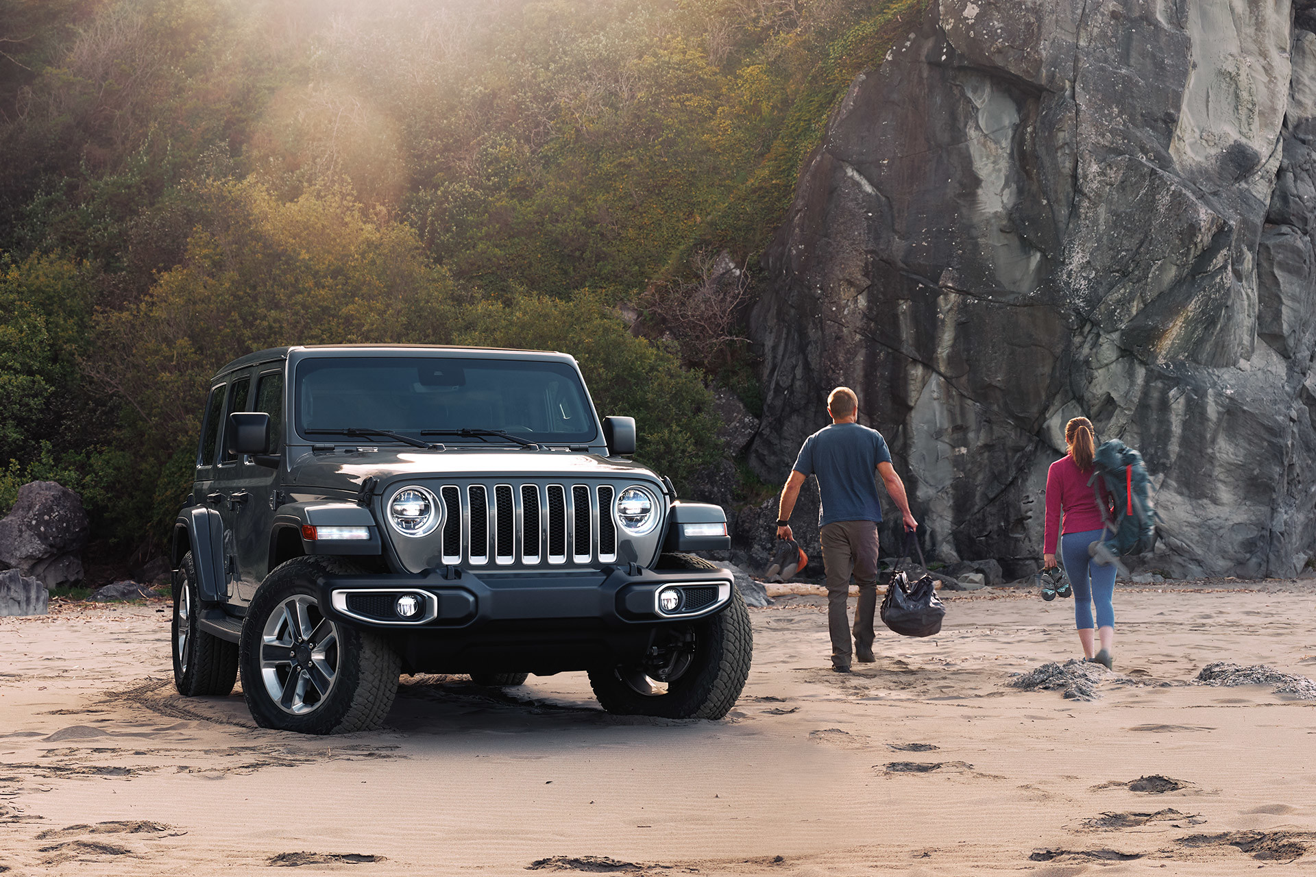 The 2020 Jeep Wrangler parked on a sand beach beside two people
