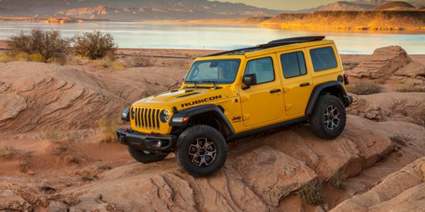 Jeep Wrangler 2020 jaune parcourant un terrain rocheux au coucher du soleil