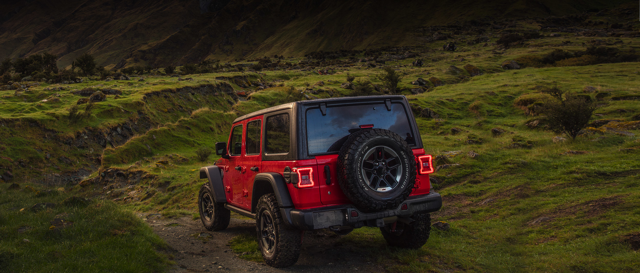 Rear quarter view of the red 2020 Jeep Wrangler parked on a dirt road facing mountains during sunset