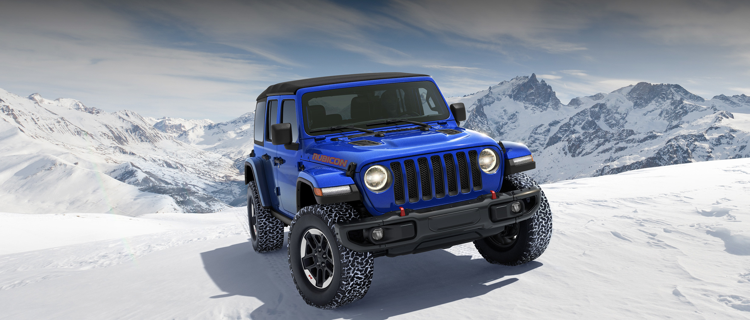 Front view of the 2020 Jeep Wrangler JL Rubicon in blue parked on a snow-covered mountain peak