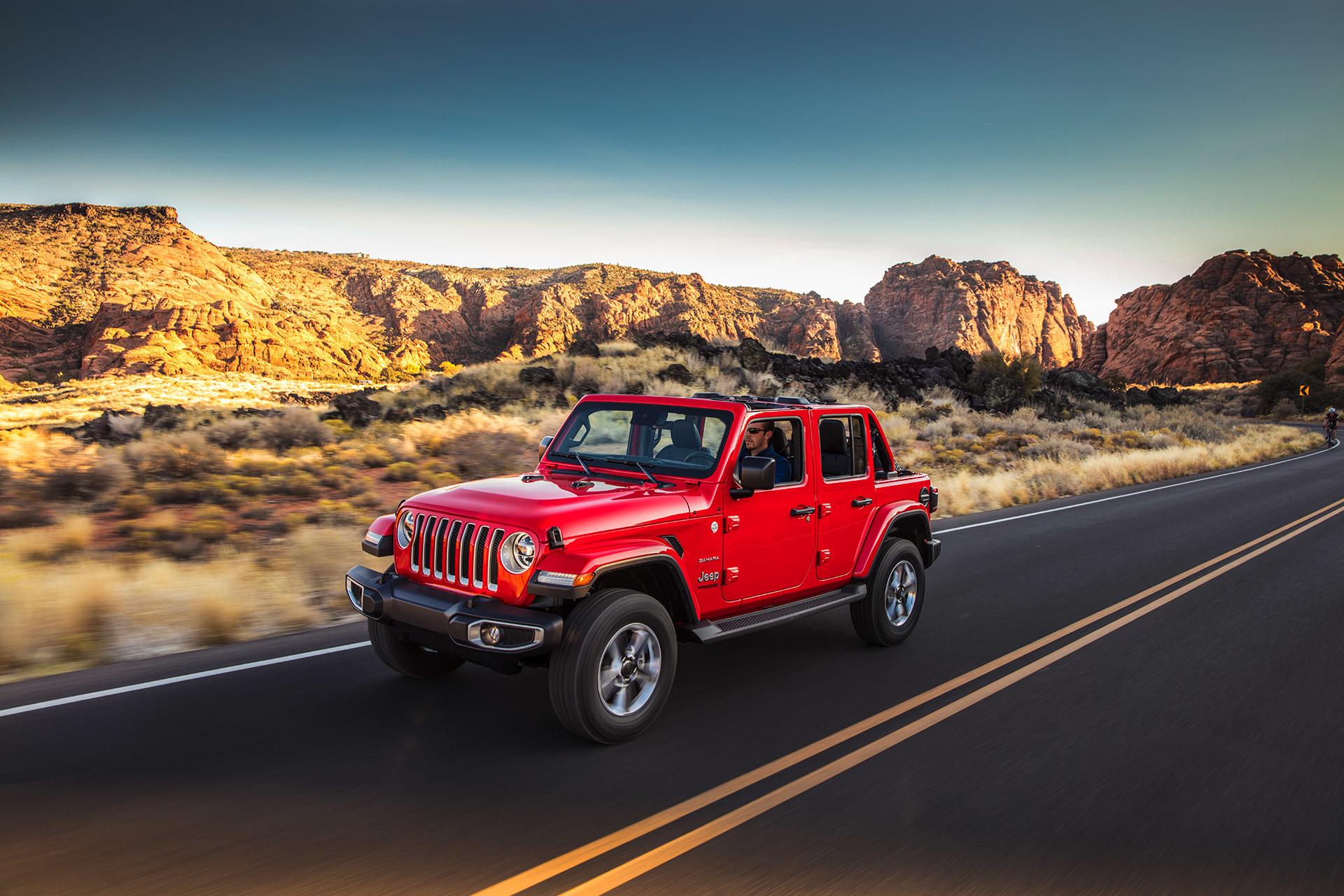 Red 2021 Wrangler driving on a desert highway.
