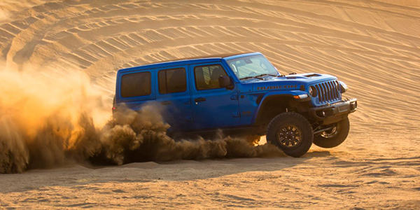 Blue Jeep Wrangler Rubicon 392 driving through the desert.