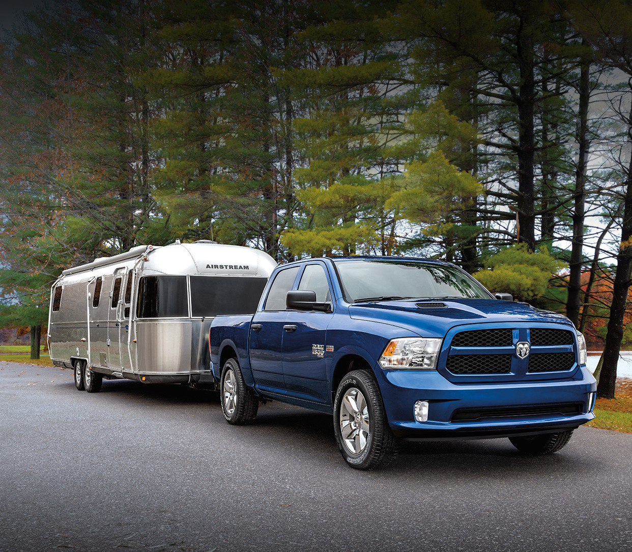 Front view of the blue 2019 Ram 1500 Classic towing a camping trailer in a forest