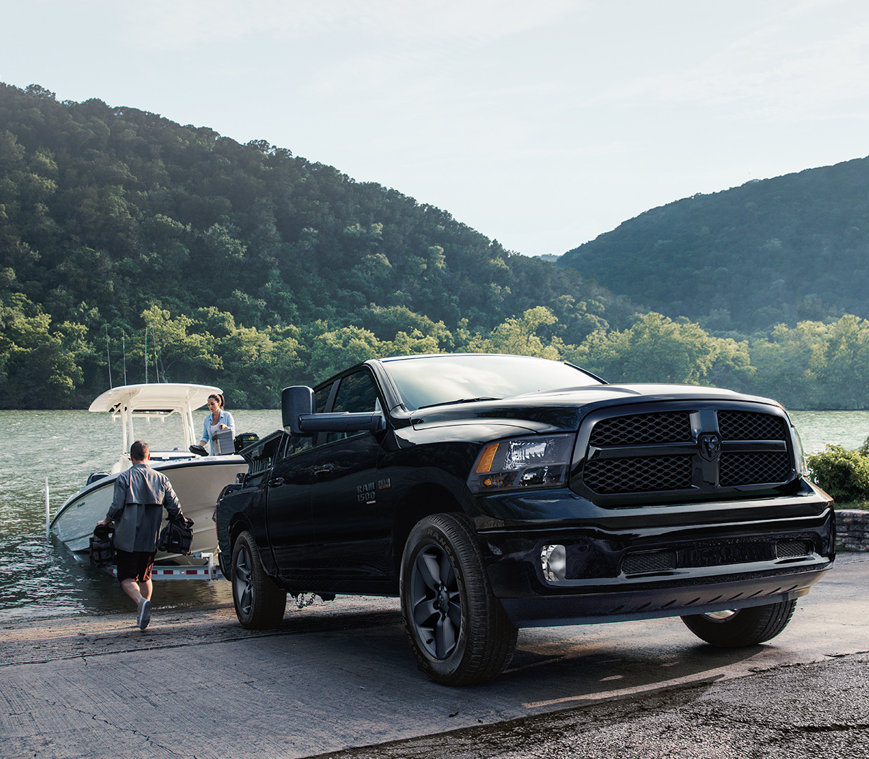 Black 2019 Ram 1500 Classic towing a boat out of a river.