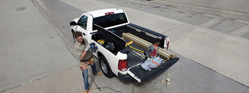 Top-down view of the white 2019 Ram 1500 parked, with the rear cargo door open and a worker walking beside the vehicle