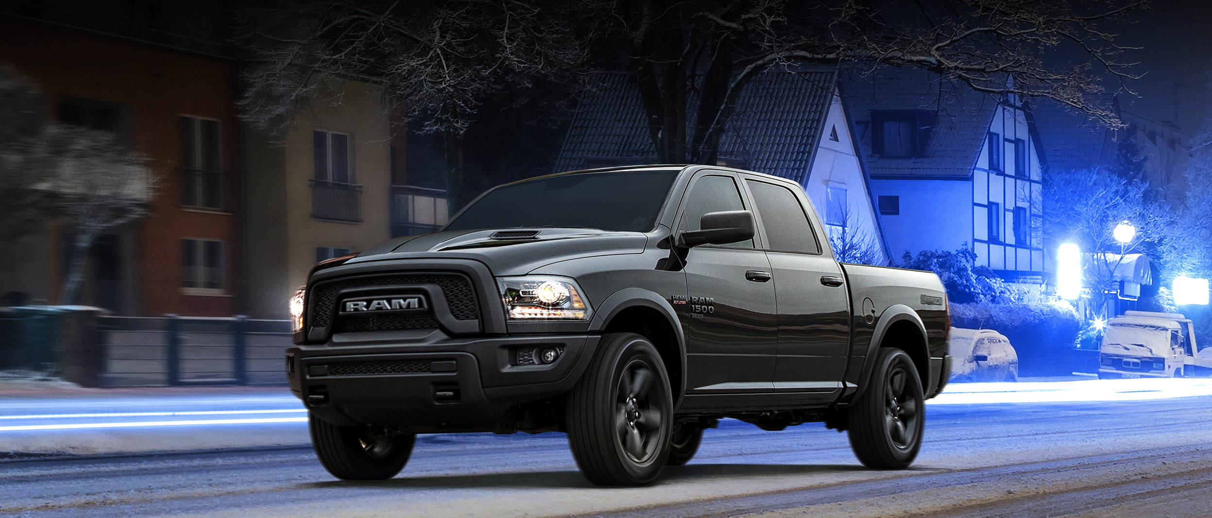A black 2020 Ram 1500 Classic Warlock driving down a snow-covered street at night
