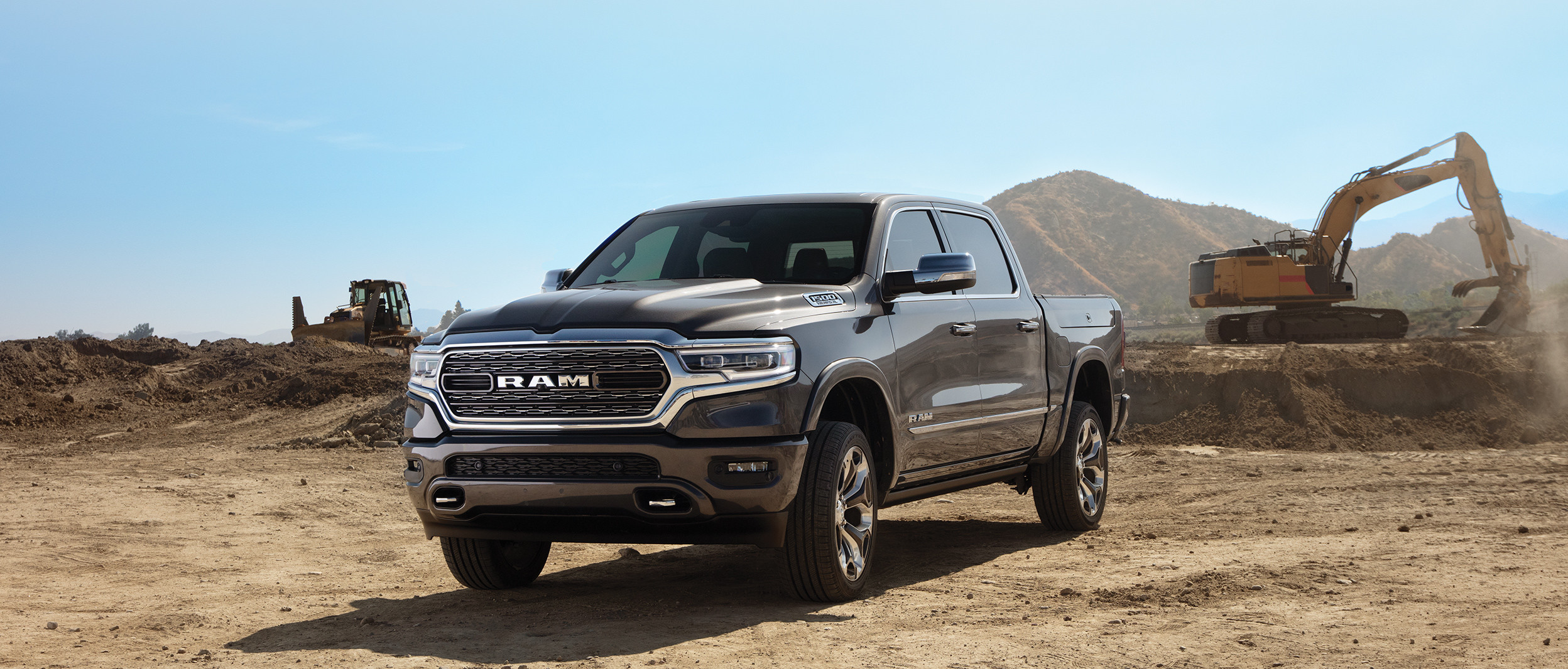 Black 2019 Ram 1500, parked on the dirt in a construction zone.