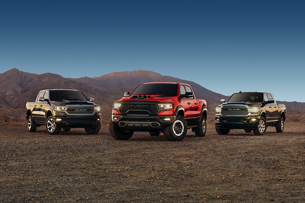 Ram 1500, Ram 1500 TRX and Ram 2500 are parked side-by-side on a desert plain with bare mountains and dark blue sky in the background. Over the past three years,  each vehicle has had its turn to win MotorTrend Truck of the Year.