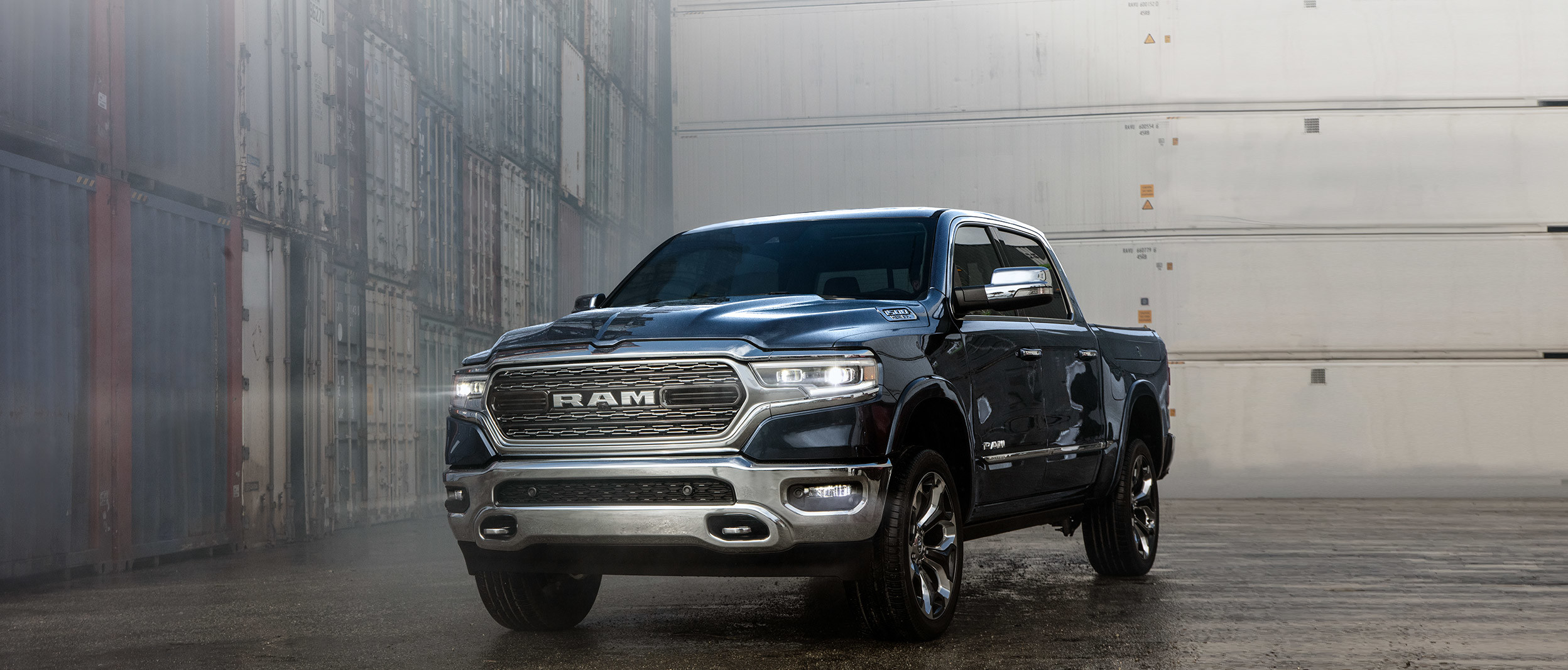 Black 2020 Ram 1500, parked in a large warehouse with cargo containers in the background.