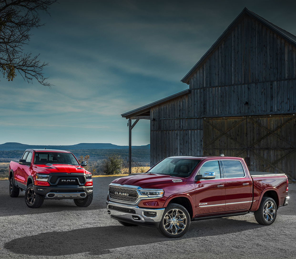 Two 2020 Ram 1500 parked in front of a barn.