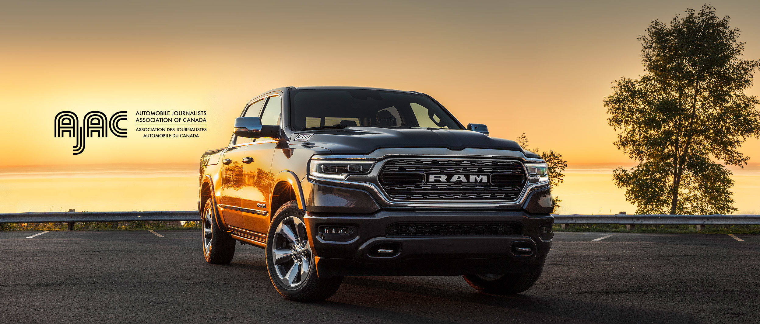 Front view of the 2020 Ram 1500 in black parked in front of the lake at sunset with the AJAC logo on top.