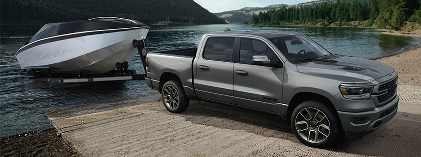 Silver 2020 Ram 1500 pulling a boat out of a lake.