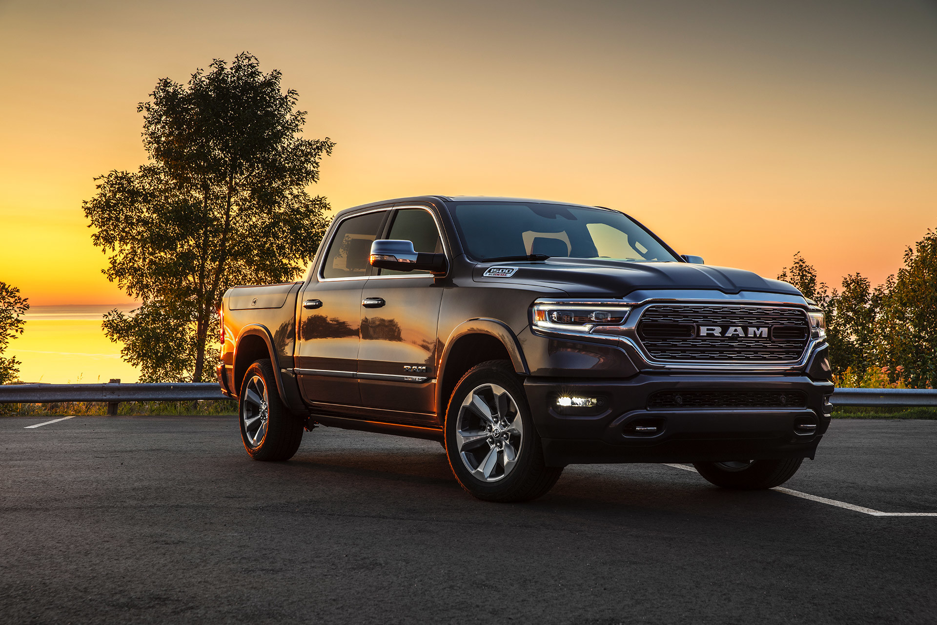 2021 Ram 1500 driving on a road at sunset.