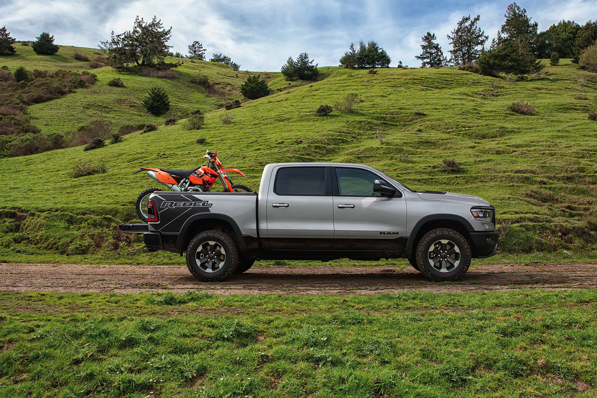 Silver 2021 Ram 1500 parked on a dirt road with a dirt bike in the bed and tailgate down.