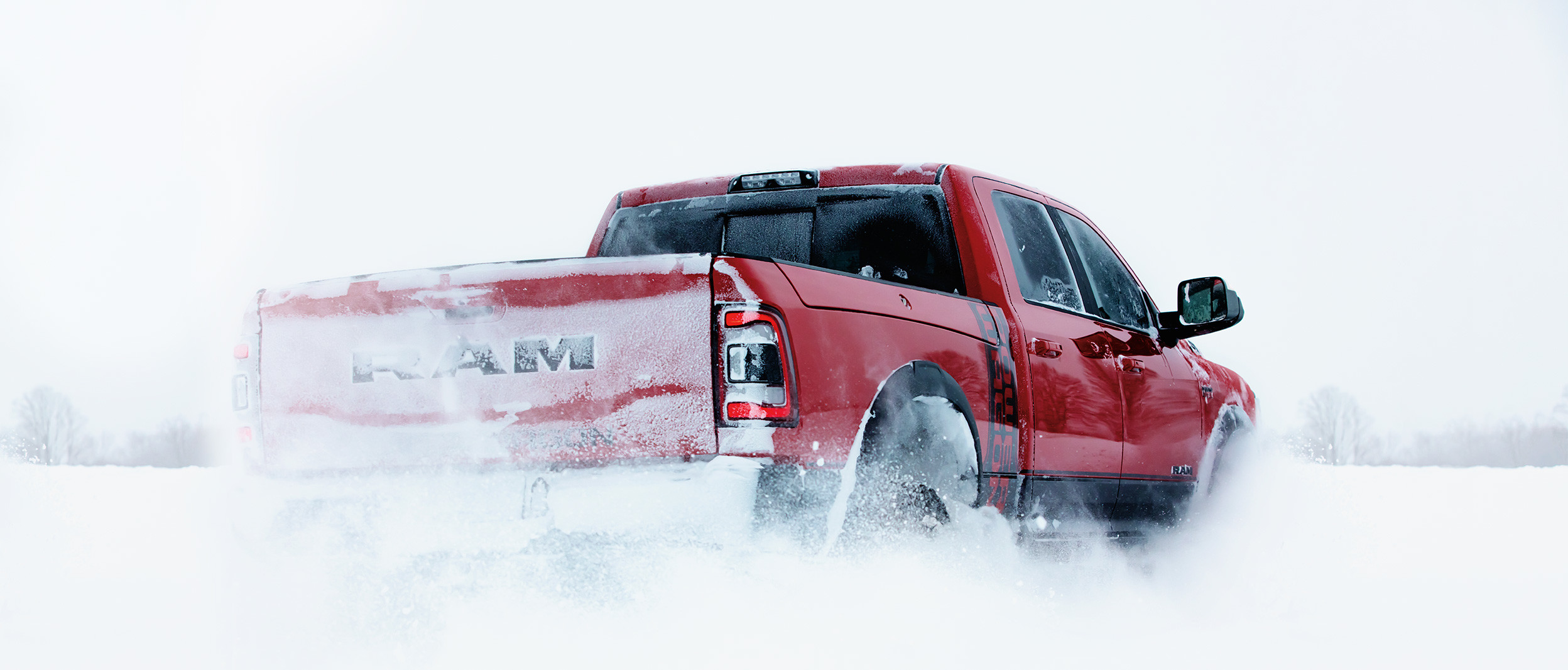 Rear view of the red 2020 Ram 2500 Rebel driving through snow