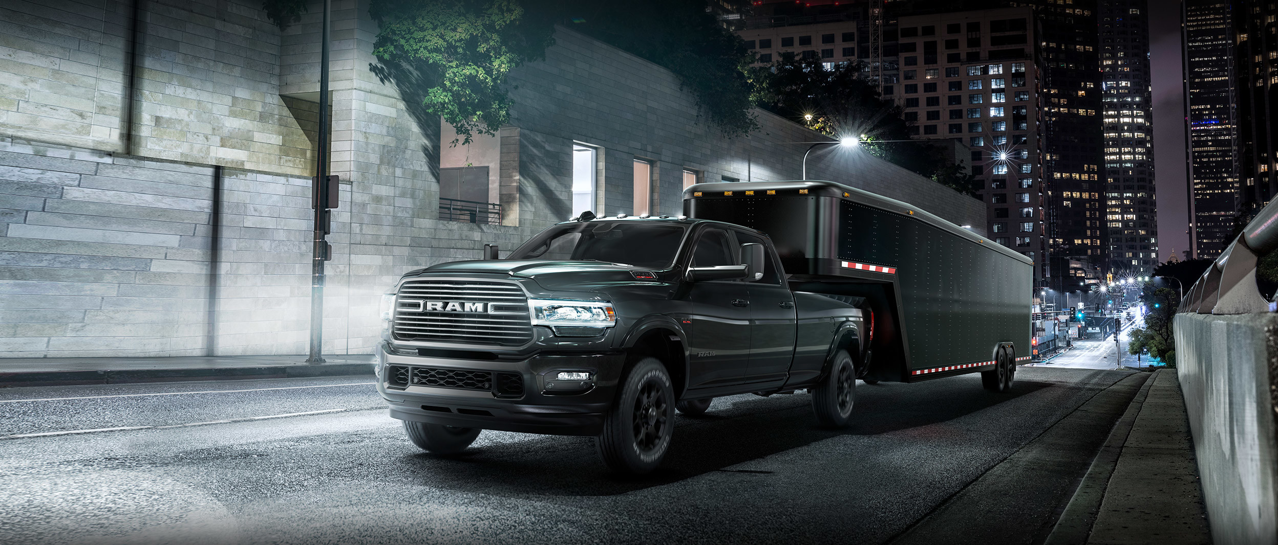 Front three quarter view of the New 2019 Ram 2500 in steel metalic colour towing a trailer on a city street at night