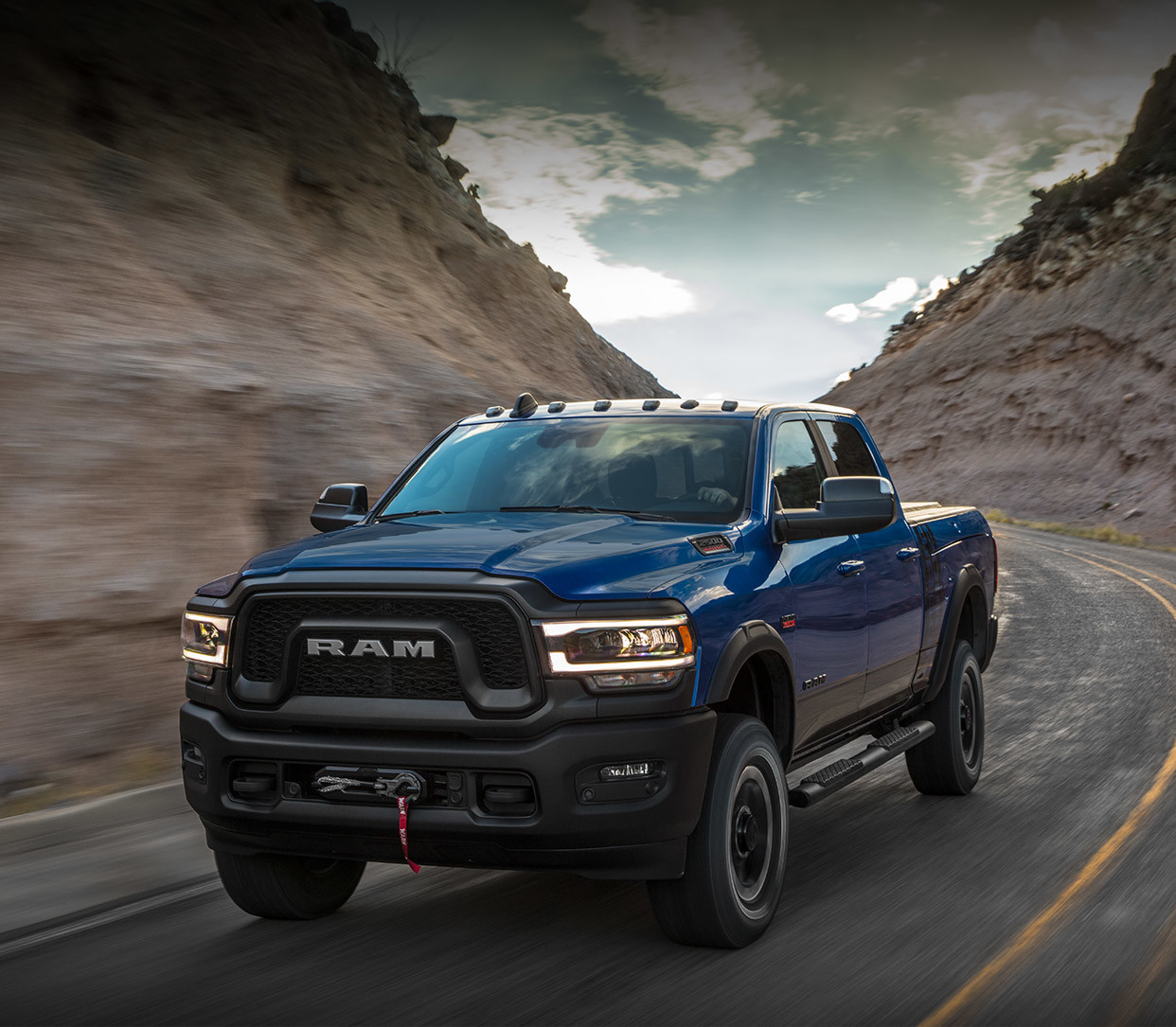 Front three quarter view of the new 2019 Ram 2500 in patriot blue pearl colour being driven on a country road