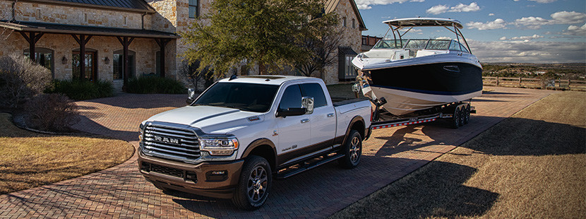 Front quarter view of white the new 2019 Ram 2500 towing a boat trailer parked in a drive way