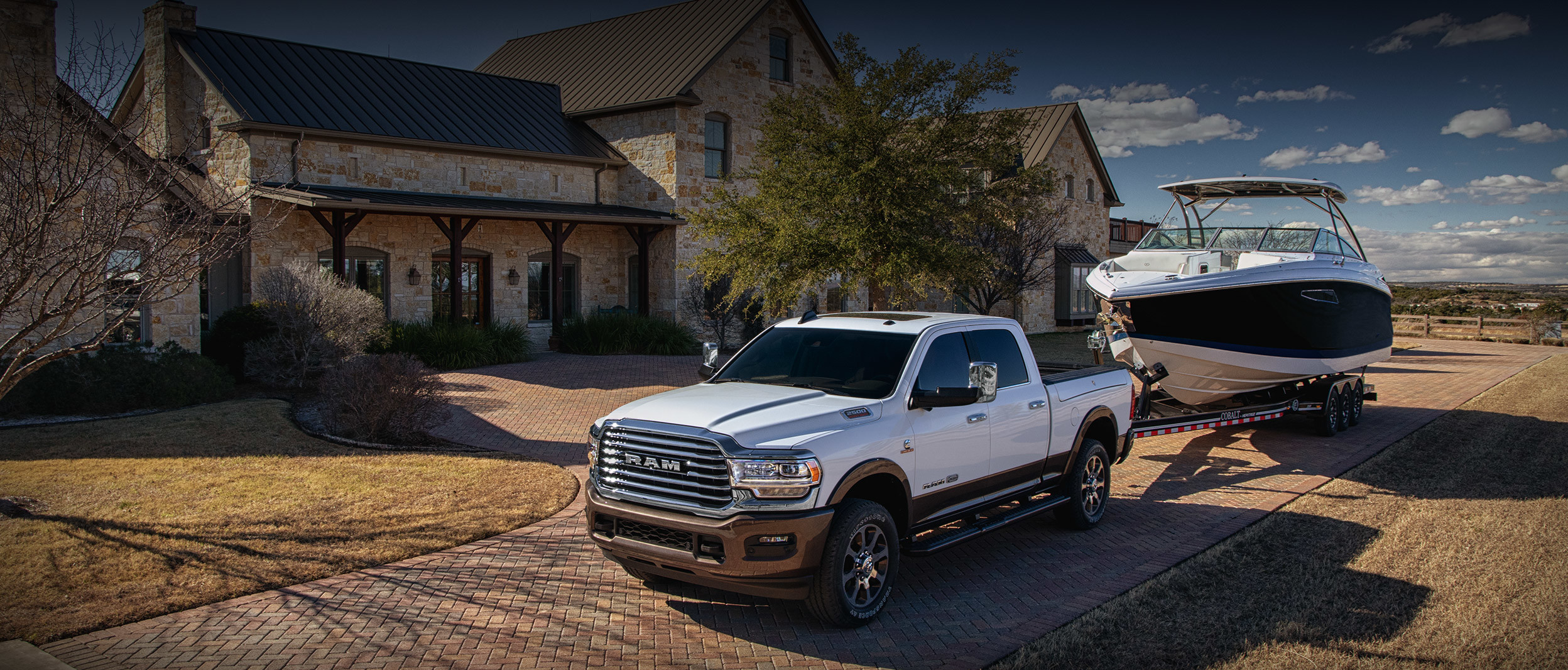 The 2020 Ram 2500 parked on a driveway while towing a boat