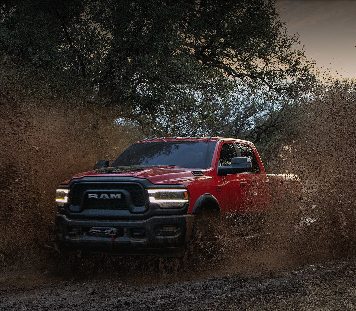 The 2020 Ram 2500 passing the muddy road through trees