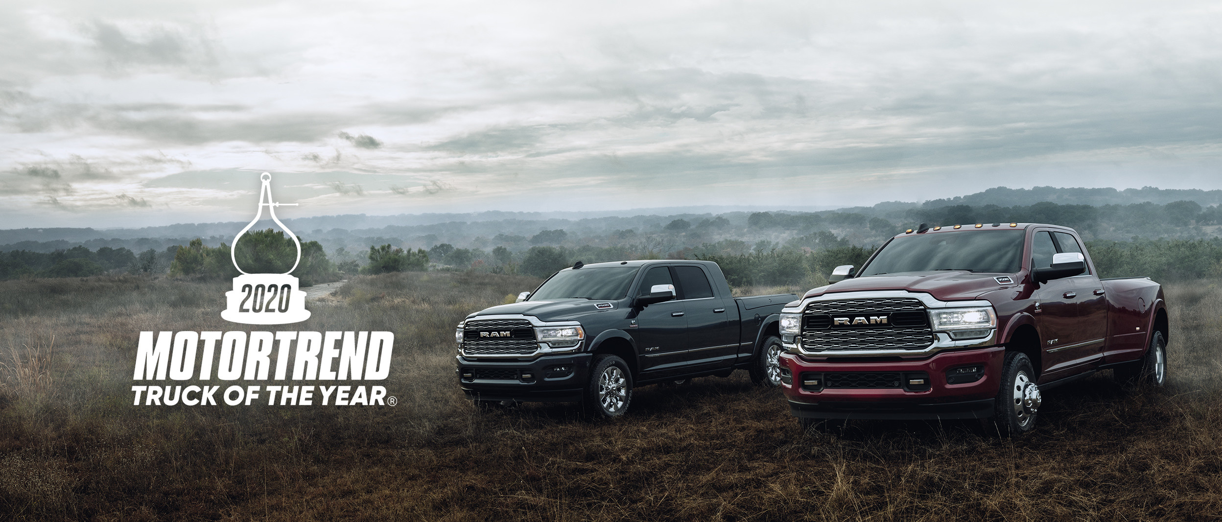 The 2020 Ram 2500 and 1500 parked on in the grass.