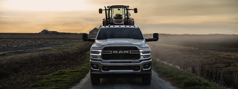 The 2020 Ram 2500 with a crawler loader at the back driving through plains