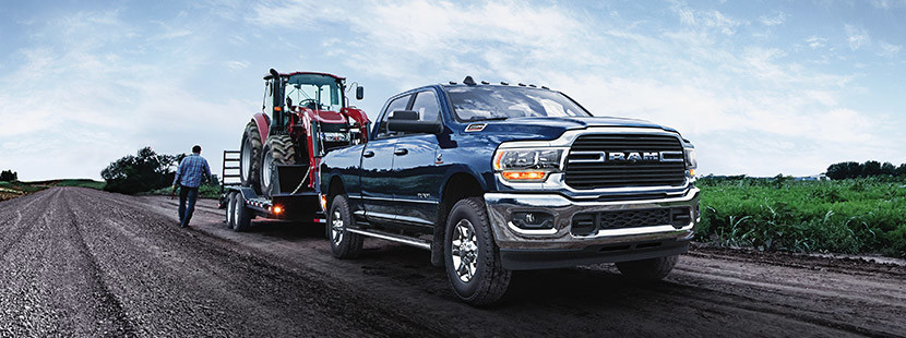The 2020 Ram 2500 towing a crawler loader parked on the side of the dirt road beside plains