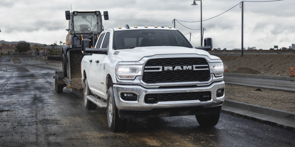 White 2021 Ram 2500 towing an excavator