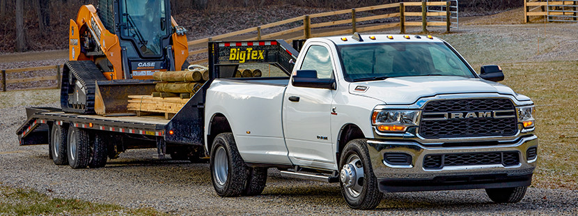 2019 Ram 3500 exterior pulling a construction vehicle.