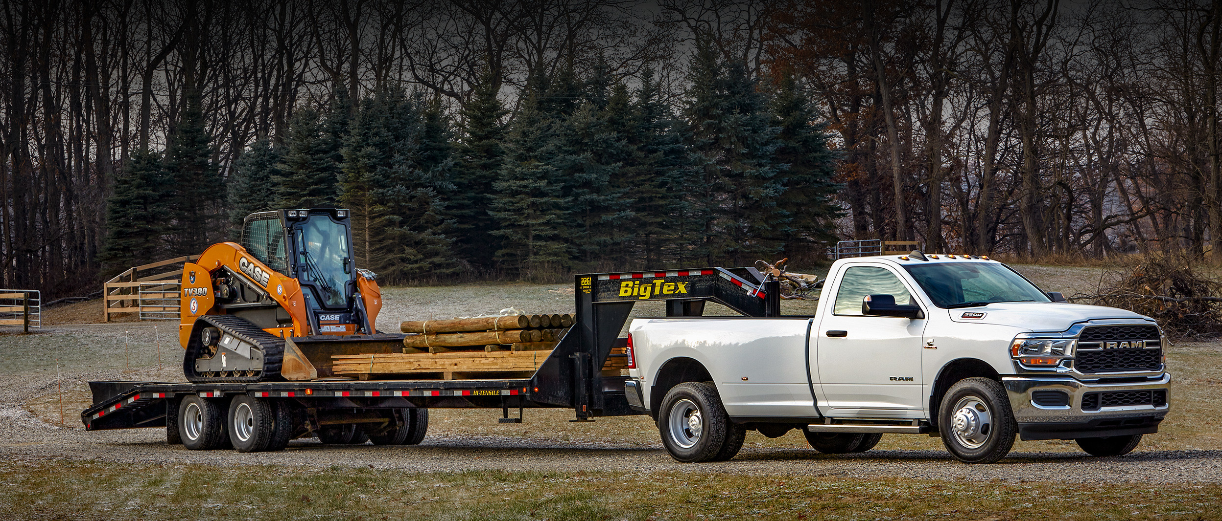 White 2020 Ram 3500 hauling a black trailer carrying wood and a skid steer loader.
