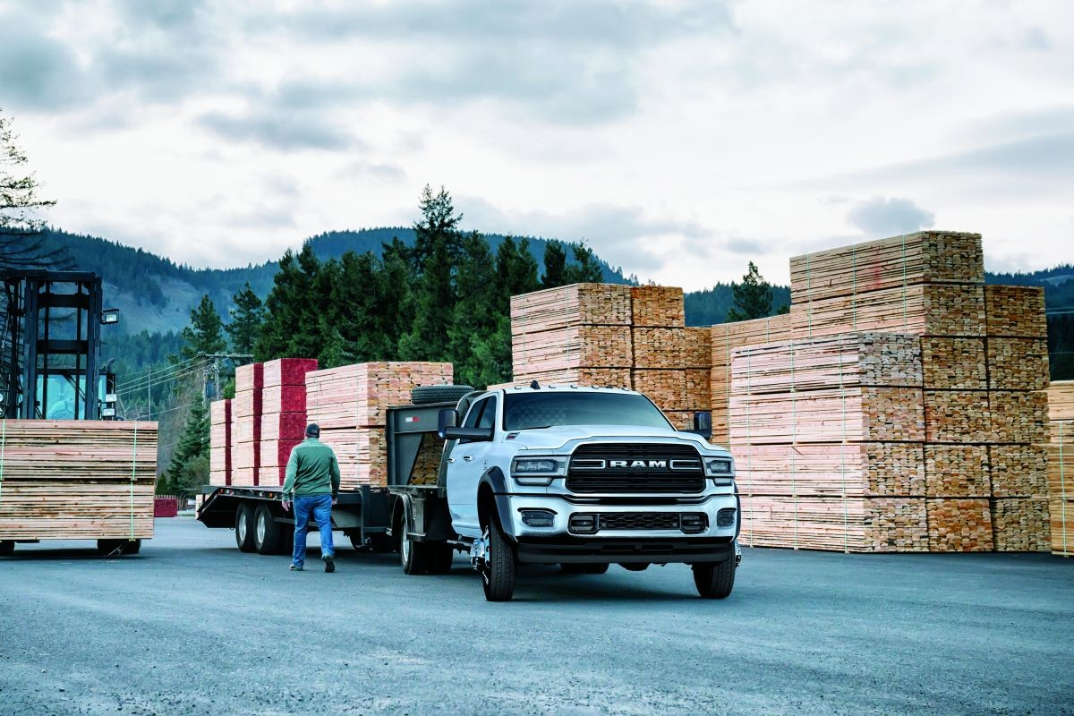A 2019 Ram 5500 Chassis Cab hauling a two-axle trailer stacked with lumber.