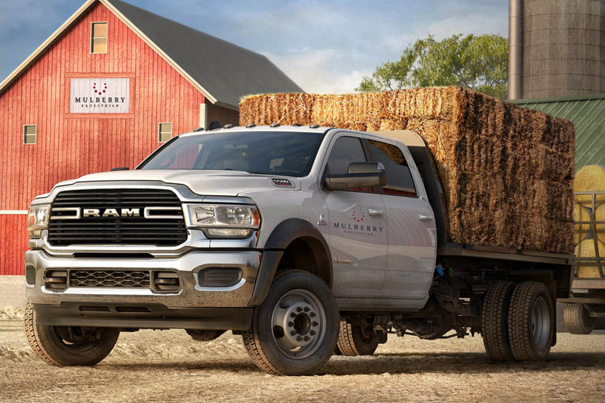 A white Ram 4500 Chassis Cab with flat rancher upfit hauls bales of hay on a farm.